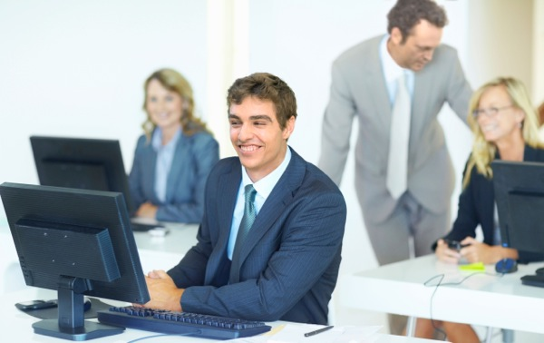 Smiling business man sitting at his computer desk